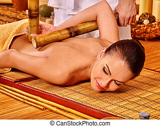 Woman getting bamboo massage. - Young woman getting long...