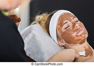 Woman getting chocolate mask treatment in spa - Beautician...