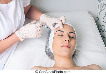 Woman getting cosmetic injection in her face on clinical center