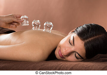 Woman Getting Cupping Treatment At Spa - Woman Lying On...