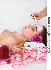 Woman getting facial mask at spa studio