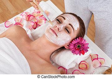 Woman getting facial mask at spa studio