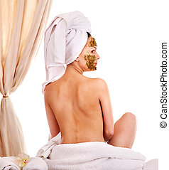 Woman getting facial mask in spa .