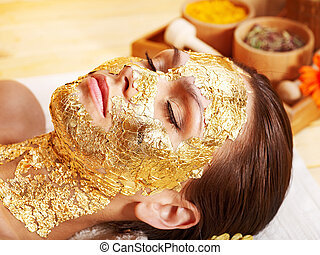 Woman getting facial mask . - Woman getting gold facial mask...
