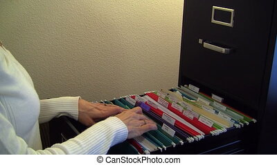 Woman getting file from cabinet