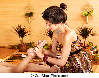 Woman getting foot massage in bamboo spa. - Young woman...