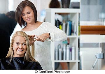 Woman Getting Haircut At Parlor