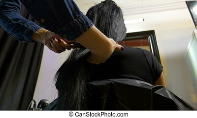 Woman getting her long brunette hair brushed at beauty parlor