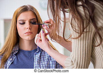 Woman getting her make-up done in beauty salon