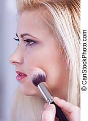 Woman getting her make up done with brush