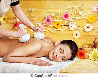 Woman getting herbal ball massage. - Woman getting herbal...