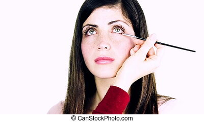 Woman getting makeup on eyes
