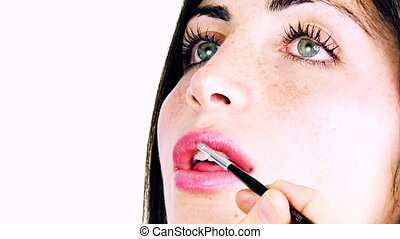 woman getting makeup on lips