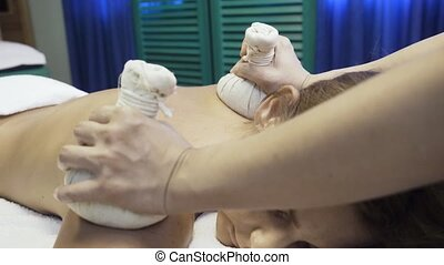 Woman getting massage with hot herbal bags. - Young woman...