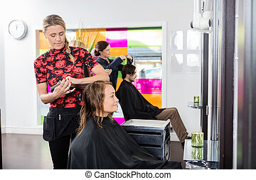 Woman Getting New Haircut By Hairstylist At Parlor