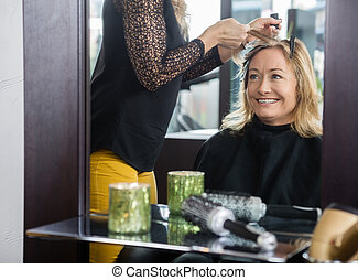 Smiling mature woman getting her new hairstyle in beauty parlor