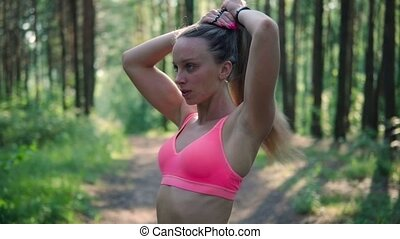 woman getting ready to run - Young athletic woman collects...