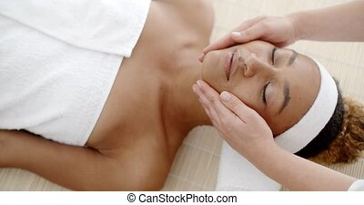 Top view of beautiful young woman lying on back while massage therapist massaging her face