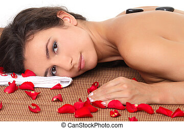 Woman getting spa treatment with black stone and rose petals
