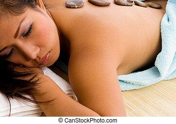 woman getting stone massage treatment