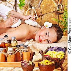 Woman getting thai herbal compress massage . - Woman getting...