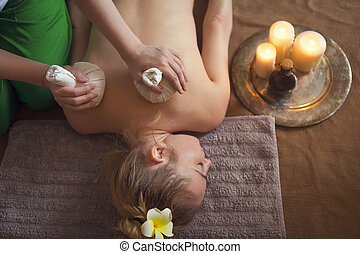 Woman getting thai herbal compress massage in spa. Close up