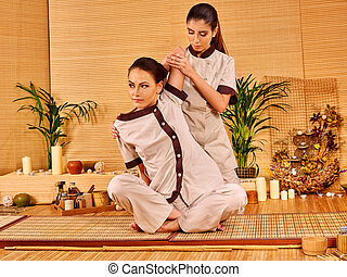 Woman getting thai herbal massage ball. - Young woman...