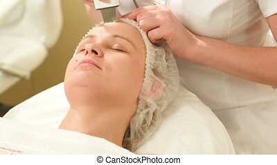 Woman getting ultrasonic face cleaning at beauty spa