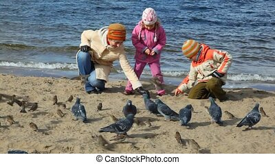 woman, girl and boy feeds pigeons