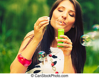 Woman girl blowing soap bubbles outdoor.