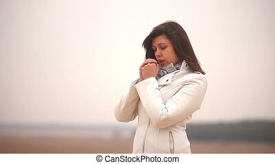 woman girl cold rubs his hands blowing autumn nature steppe...