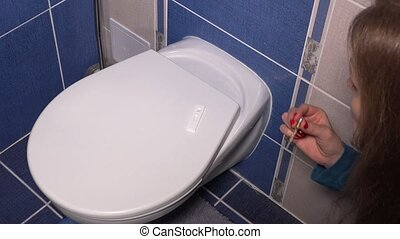 woman girl doing pregnancy test with pipette in bathroom and waiting for result