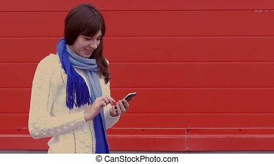 woman girl holding a smartphone in a jacket and a scarf social networks media