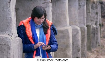 woman girl holding a smartphone in jacket scarf social networks media