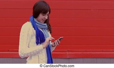 woman girl holding a smartphone phone in a jacket and a scarf social networks media