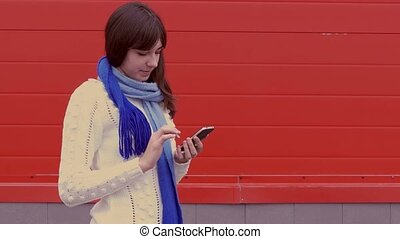 woman girl holding a smartphone phone in a jacket and scarf social networks media