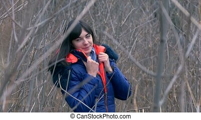 woman girl in jacket and a scarf standing in the dry branches of young trees