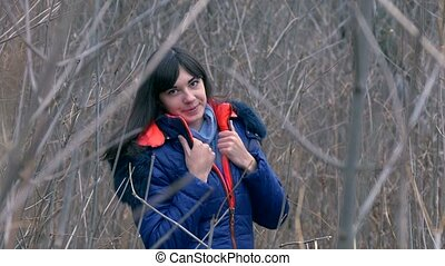 woman girl in jacket and scarf standing in the dry branches...