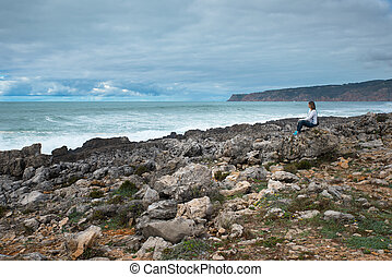 Woman, girl sitting on the Atlantic Ocean