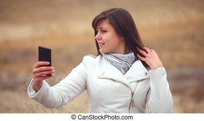 woman girl smartphone makes self phone sitting on dry tree nature autumn