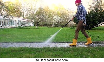 woman girl spray clean path with pressure washer in garden. 4K