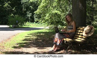 Woman girl working with laptop on park bench having wireless internet connection problems. 4K