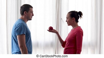 Woman gives apple to man