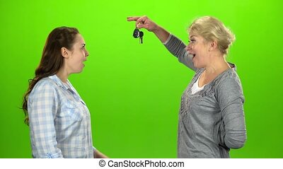 Woman gives the keys to her daughter. Green screen. Side...