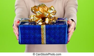 Woman gives to a box with a gift. Pleasant surprise.