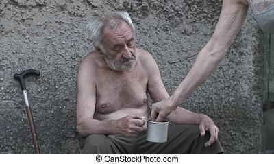 Woman giving a coin to old poor man - Homeless old man with...