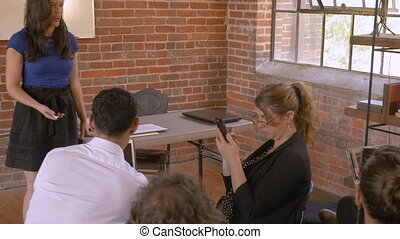 Woman giving a presentation while audience ignores her all using technology