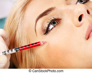 Woman giving botox injections.