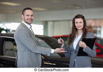 Woman giving car keys to a man