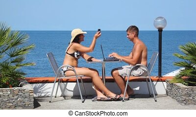 woman giving cell phone to man sitting at table with notebook, sea in background